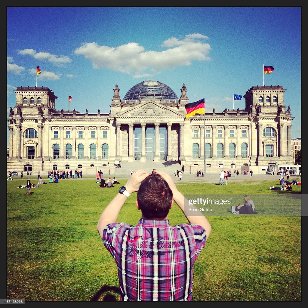 A visitor photographs the Reichstag on April 28, 2014 in Berlin, Germany. The Reichstag, home of the Bundestag, the German parliament, is among the city's major landmarks and a favourite tourist destination.