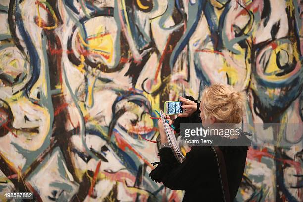 A visitor photographs the work 'Mural' 1943 by Jackson Pollock during a press preview of the 'Jackson Pollock's Mural Energy Made Visible' exhibition...
