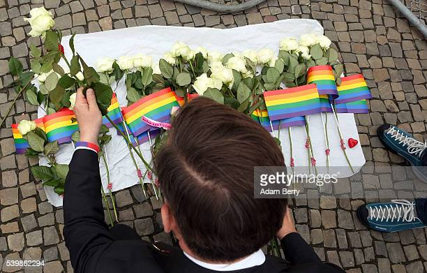 A visitor places flowers at a makeshift memorial during a vigil for victims of a shooting at a gay nightclub in Orlando Florida the previous day in...