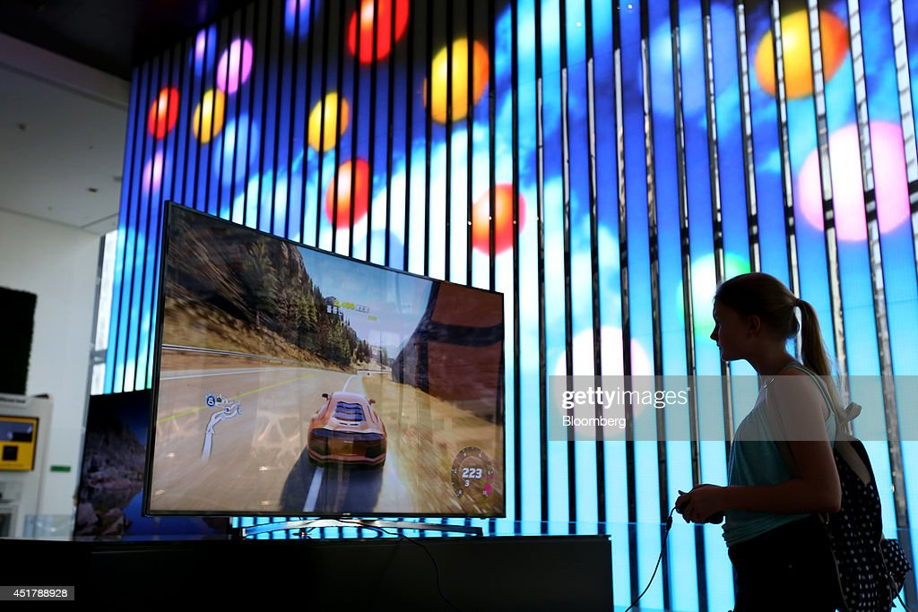 A visitor plays a video game in front of a light wall at the Samsung Electronics Co. d'light showroom in Seoul, South Korea, on Monday, July 7, 2014. Samsung Electronics is scheduled to report operating profit and sales figures on July 8. Photographer: SeongJoon Cho/Bloomberg via Getty Images