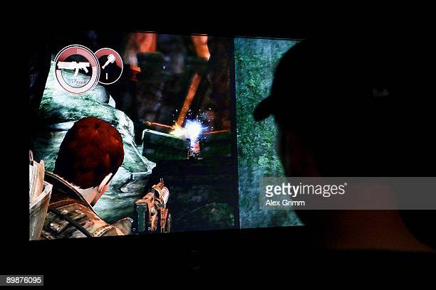 A visitor plays 'Dark Void' at the stand of Japanese video game company Capcom during the 'gamescom' Europe's biggest trade fair for interactive...