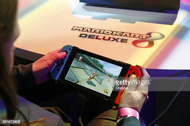 A visitor plays the 'Mario Kart 8 Deluxe' video game on a Nintendo Switch games console during the new console's unveiling by Nintendo Co on January...