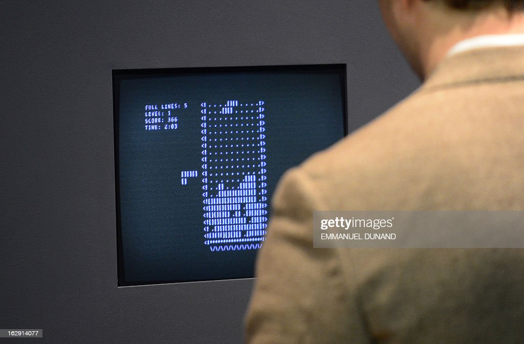 A visitor plays the video game Tetris (1984) during an exhibition preview featuring 14 video games acquired by The Museum of Modern Art (MoMA) in New York, March 1, 2013. The MoMA acquired 14 video games entering its collection as part of an ongoing research on interaction design.