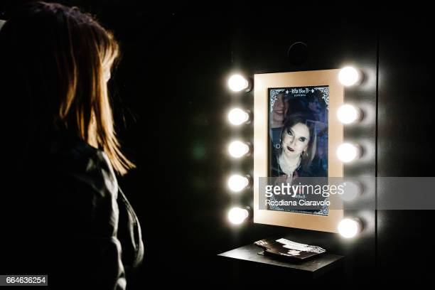 A visitor plays with the app to apply on herself digital make up inspired by the style of Kat Von D at the event during the Kat Von D Inaugurates...