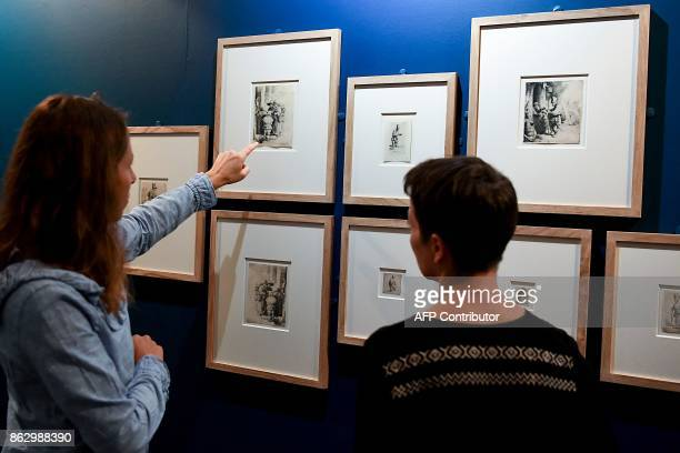 A visitor points to Dutch painter and printmaker Rembrandt's 1648 etching 'Beggars receiving alms at the door of a house' during an exhibition of a...