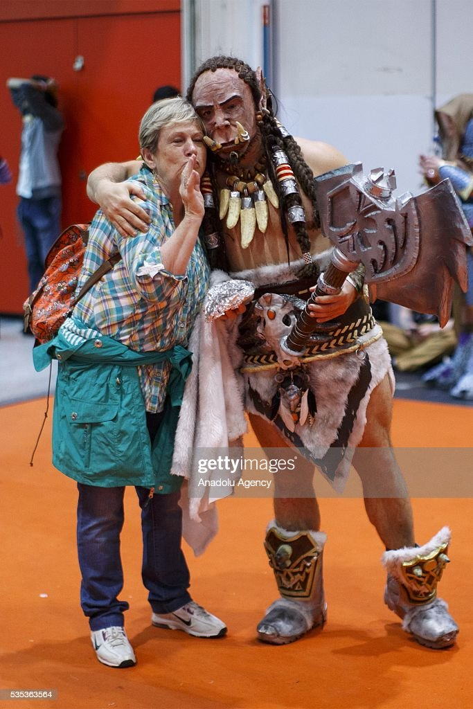 A visitor pose for a photo with a Warcraft cosplayer during MCM Comic Con at ExCeL convention centre in London, England on May 29, 2016.