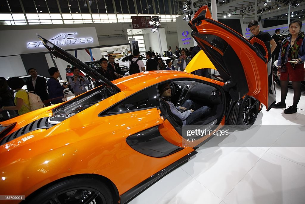 A visitor (C) poses for a photo in a Mclaren car on display at the China International Exhibition Center new venue during the 'Auto China 2014' Beijing International Automotive Exhibition in Beijing on April 20, 2014. Leading automakers are gathering in Beijing for the kickoff of China's biggest car show, but lackluster growth and environmental restrictions in the world's largest car market have thrown uncertainty into the mix. More than 1,100 vehicles are being showcased at the auto show, which opens to the public on April 21. CHINA