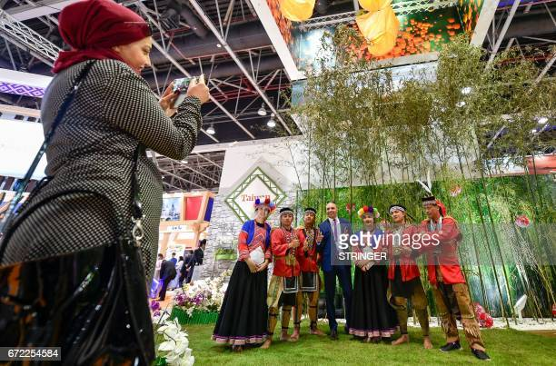 A visitor poses for a photo with exhibitors at Taiwan pavilion during the Arabian Travel Market 2017 at the Dubai World Trade Centre on April 24 2017...