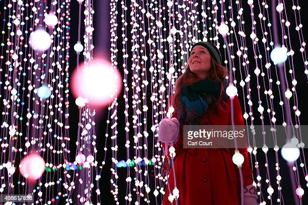 A visitor poses for a photograph amongst illuminations at The Royal Botanic Gardens at Kew Gardens on November 24 2015 in London England Kew Garden's...