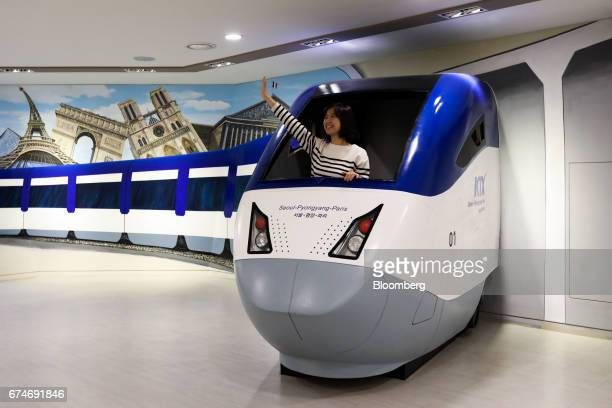 A visitor poses for a photograph inside a mockup of the Korea Train Express bullet train marked with SeoulPyongyangParis at the Odusan Unification...