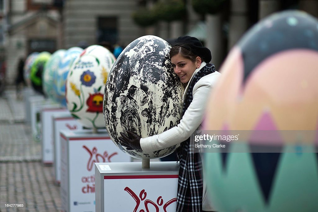 A visitor poses for a photograph with an egg entitled 'How Mind Came Into The World' by Whitney McVeigh one of the giant fibreglass easter eggs on display in Covent Garden before the Big Egg Hunt on March 22, 2013 in London, England. Each egg is two and a half feet tall and designed by a leading artist.