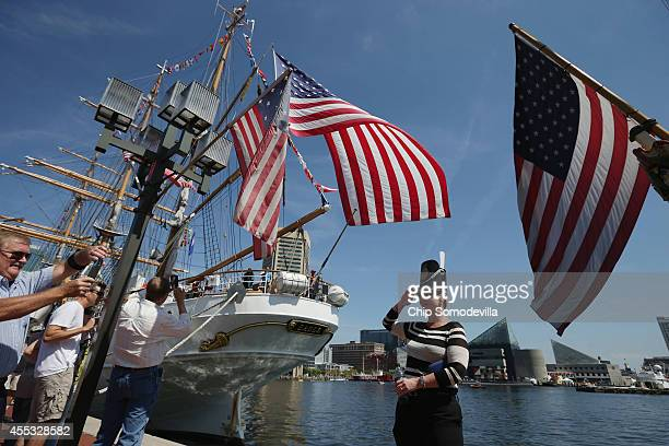 A visitor poses for a photograph with the US Coast Guard Cutter Eagle where it is docked in the Inner Harbor as part of the Star Spangled Spectacular...