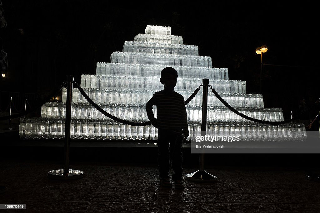A visitor poses for a picture next to a light installation during the annual Jerusalem Festival of Light on June 5, 2013 in Jerusalem, Israel. During the festival light installations are projected onto the historic buildings of Jerusalem's Old City.