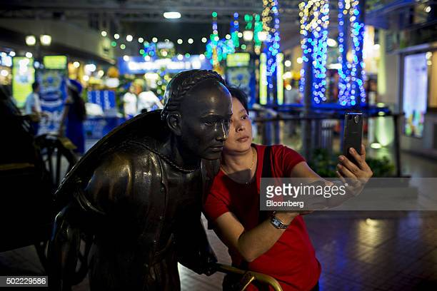A visitor poses for a selfie photograph with a statue at AsiatiqueThe Riverfront openair mall in Bangkok Thailand on Friday Dec 18 2015 Thai economic...