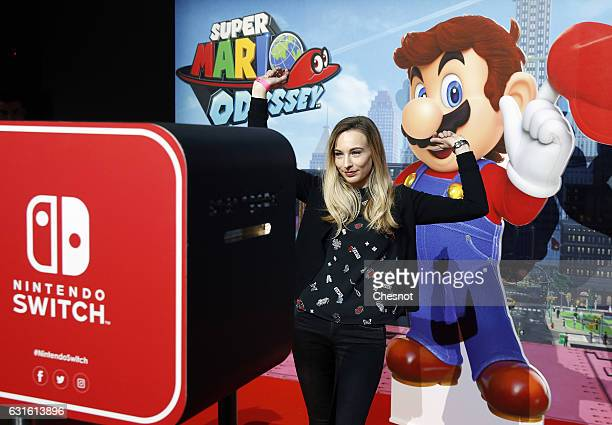 Visitor poses in front of a signage for 'Super Mario Odyssey' new video game during the new console's unveiling 'Nintendo Switch' by Nintendo Co on...