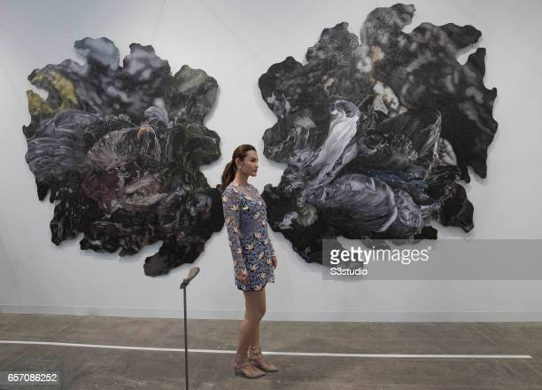 A visitor poses in front of artist Patricia Perez Eustaquio's 'Let Us Build a Mountain VIII 2017' during Art Basel Hong Kong 2017 at Hong Kong...