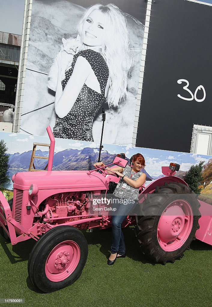 A visitor poses on a pink farm tractor for a friend's snapshot at the 2012 Bread & Butter fashion trade fair at former Tempelhof Airport on July 6, 2012 in Berlin, Germany. Bread & Butter is the world's largest trade fair for street fashion.