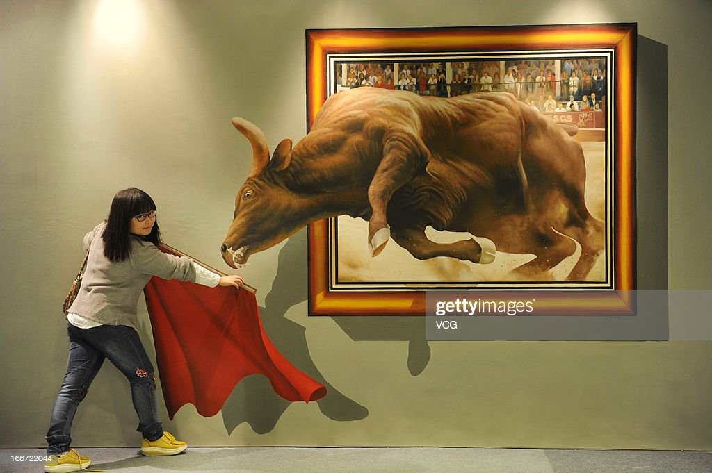 A visitor poses with a 3D painting during exhibition at the Garland Shopping Center on April 15, 2013 in Guiyang, Guizhou province of China. The free exhibition will run for a week with visitors actively encouraged to interact with the artworks.
