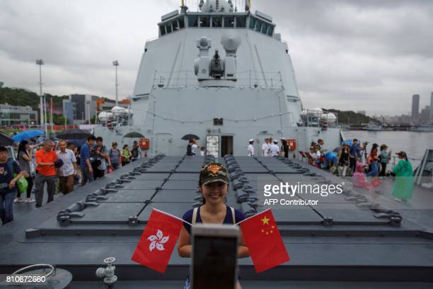 A visitor poses with the Chinese and Hong Kong flags on board the Yinchuan a People's Liberation Army Navy Type 052D destroyer at the Ngong Shuen...