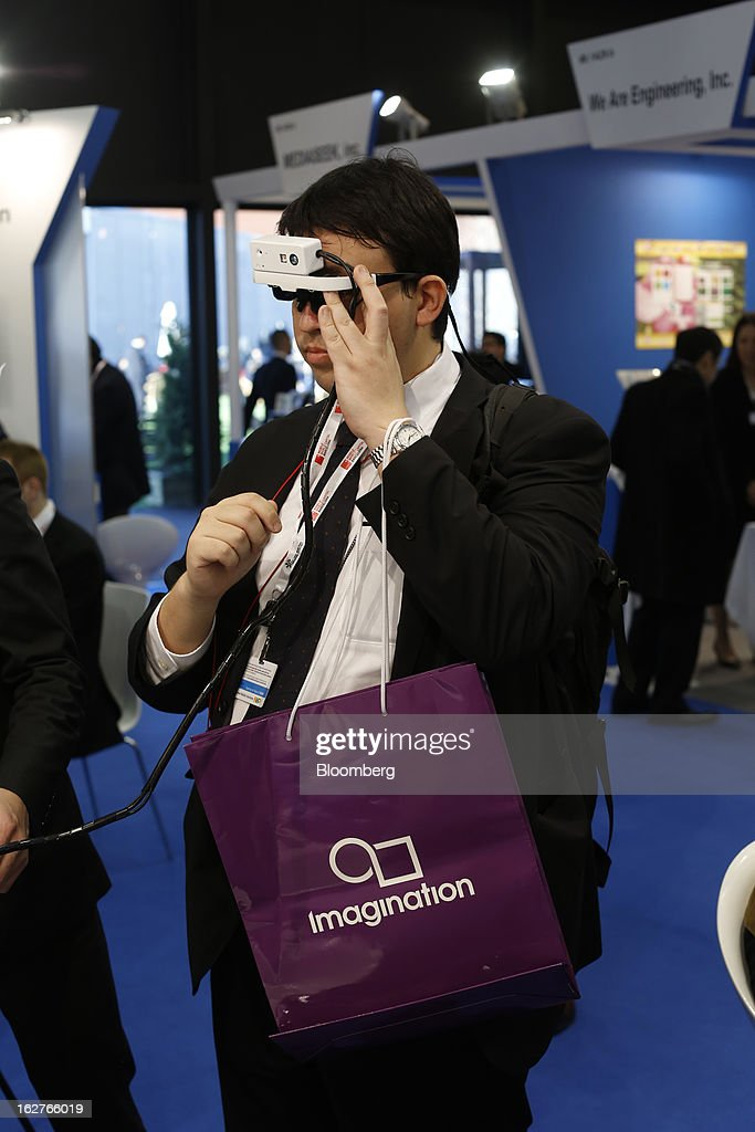 A visitor prepares to test a concept 'Viking' head mounted display device on the Brilliantservice Co. stand at the Mobile World Congress in Barcelona, Spain, on Tuesday, Feb. 26, 2013. The Mobile World Congress, where 1,500 exhibitors converge to discuss the future of wireless communication, is a global showcase for the mobile technology industry and runs from Feb. 25 through Feb. 28. Photographer: Simon Dawson/Bloomberg via Getty Images