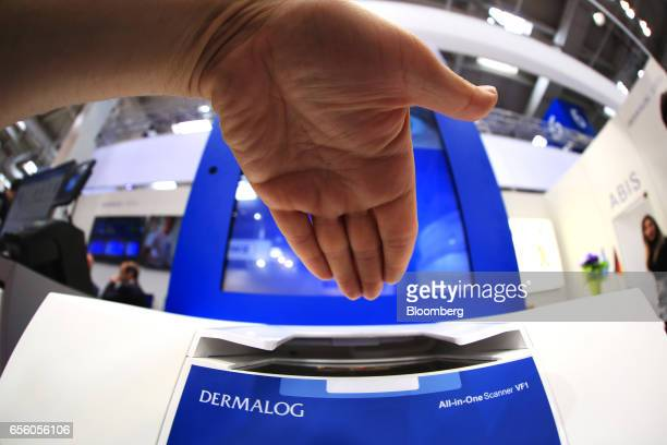 A visitor prepares to use an AllinOne VF1 fingerprint and passport scanning device at the Dermalog Identification Systems GmbH pavilion at the CeBIT...