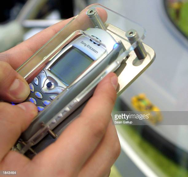 A visitor races miniature cars with a Sony Ericsson 68i mobile phone via a Bluetooth connection at the CeBIT technology trade fair March 12 2003 in...