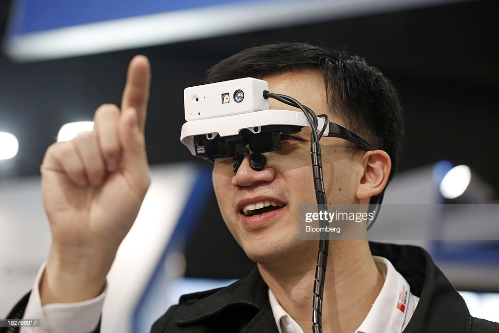 A visitor raises his finger to test a concept 'Viking' head mounted display device on the Brilliantservice Co. stand at the Mobile World Congress in Barcelona, Spain, on Tuesday, Feb. 26, 2013. The Mobile World Congress, where 1,500 exhibitors converge to discuss the future of wireless communication, is a global showcase for the mobile technology industry and runs from Feb. 25 through Feb. 28. Photographer: Simon Dawson/Bloomberg via Getty Images