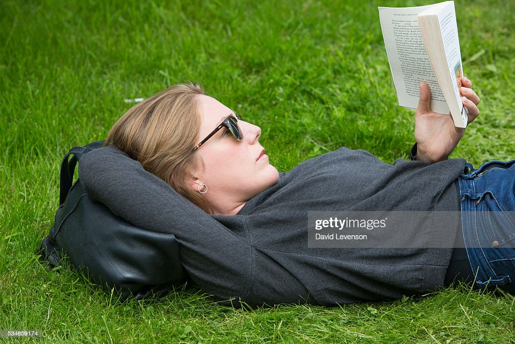 A visitor reads a book at the Hay Festival, on May 28, 2016 in Hay-on-Wye, Wales.