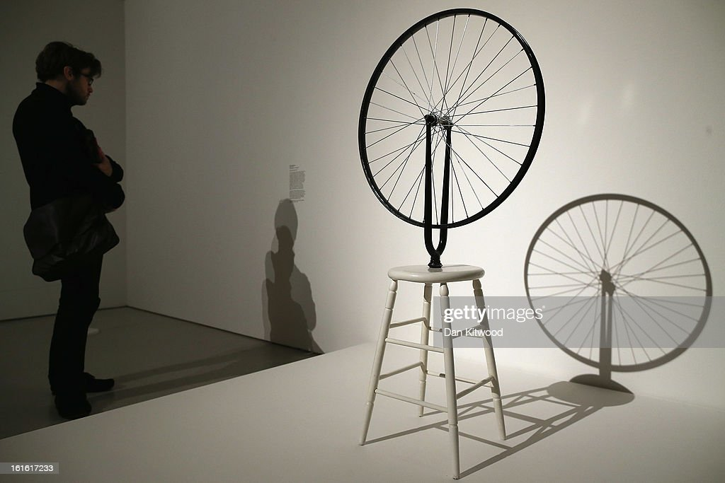 A visitor reads notes related to the piece of work by Marcel Duchamp entitled 'Bicycle Wheel' during a press preview of 'The Bride and the Bachelors'...