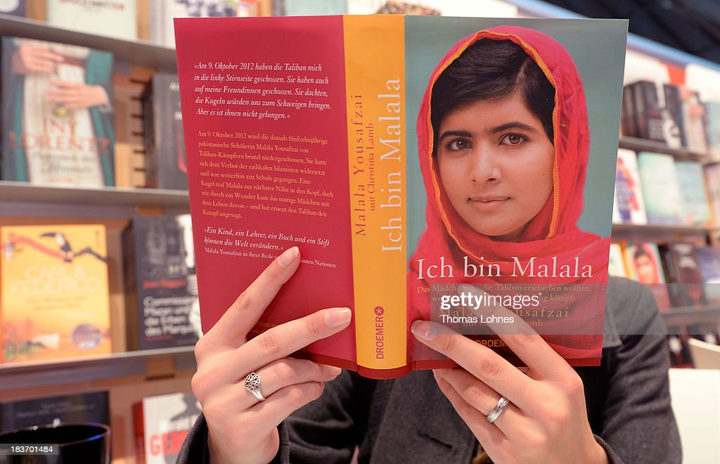 A visitor reads the book 'Ich bin Malala' (I am Malala) from <a gi-track='captionPersonalityLinkClicked' href=/galleries/search?phrase=Malala+Yousafzai&family=editorial&specificpeople=5849423 ng-click='$event.stopPropagation()'>Malala Yousafzai</a> of the 2013 Frankfurt Book Fair on October 9, 2013 in Frankfurt, Germany. This year's fair will be open to the public from October 9-13 and the official partner nation is Brazil.