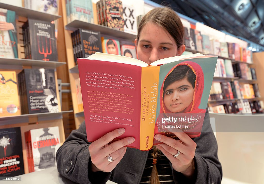 A visitor reads the book 'Ich bin Malala' (In am Malala) of <a gi-track='captionPersonalityLinkClicked' href=/galleries/search?phrase=Malala+Yousafzai&family=editorial&specificpeople=5849423 ng-click='$event.stopPropagation()'>Malala Yousafzai</a> of the 2013 Frankfurt Book Fair on October 9, 2013 in Frankfurt, Germany. This year's fair will be open to the public from October 9-13 and the official partner nation is Brazil.