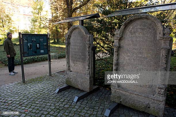 A visitor reads the information board near tombstones of Berlin's oldest Jewish cemetery October 31 2013 in the German capital's district of Mitte...