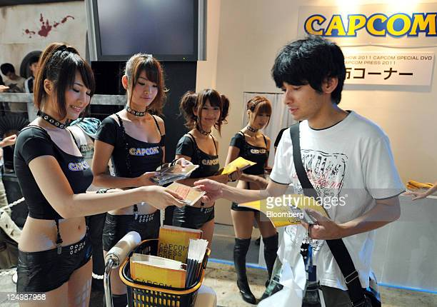 A visitor receives a DVD from a promotional staff member in the Capcom Co booth at the Tokyo Game Show 2011 at Makuhari Messe in Chiba City Japan on...