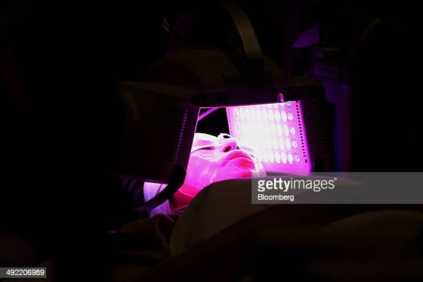 A visitor receives a facial treatment using light emitting diode at the Beautyworld Japan fair in Tokyo Japan on Monday May 19 2014 The...