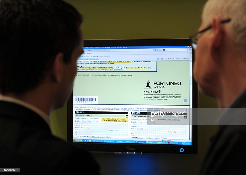A visitor receives explanations at the French online bank Fortuneo's stand during the Actionaria shareholders event in Paris on November 23, 2012. AFP PHOTO / ERIC PIERMONT
