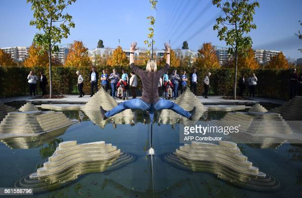 A visitor reflects herself in a mirror at the Thai 'Garden of the Mind' part of the 'Gardens of the World' international garden collection at the...
