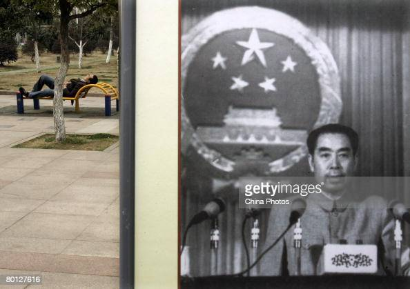 A visitor rests beside a picture featuring late Chinese premier Zhou Enlai delivering a speech during a photo exhibition on the life of Zhou to mark...