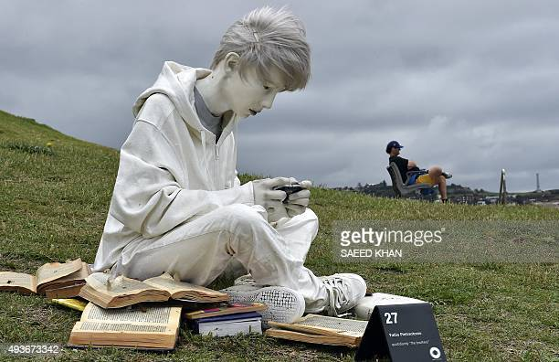 A visitor rests next to a sculpture by artist Fabio Pietrantonio at the 'Sculpture by the Sea' exhibition which runs along the Bondi to Tamarama...