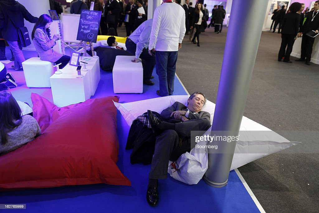 A visitor rests on cushions in the Nokia Oyj pavilion at the Mobile World Congress in Barcelona, Spain, on Tuesday, Feb. 26, 2013. The Mobile World Congress, where 1,500 exhibitors converge to discuss the future of wireless communication, is a global showcase for the mobile technology industry and runs from Feb. 25 through Feb. 28. Photographer: Simon Dawson/Bloomberg via Getty Images