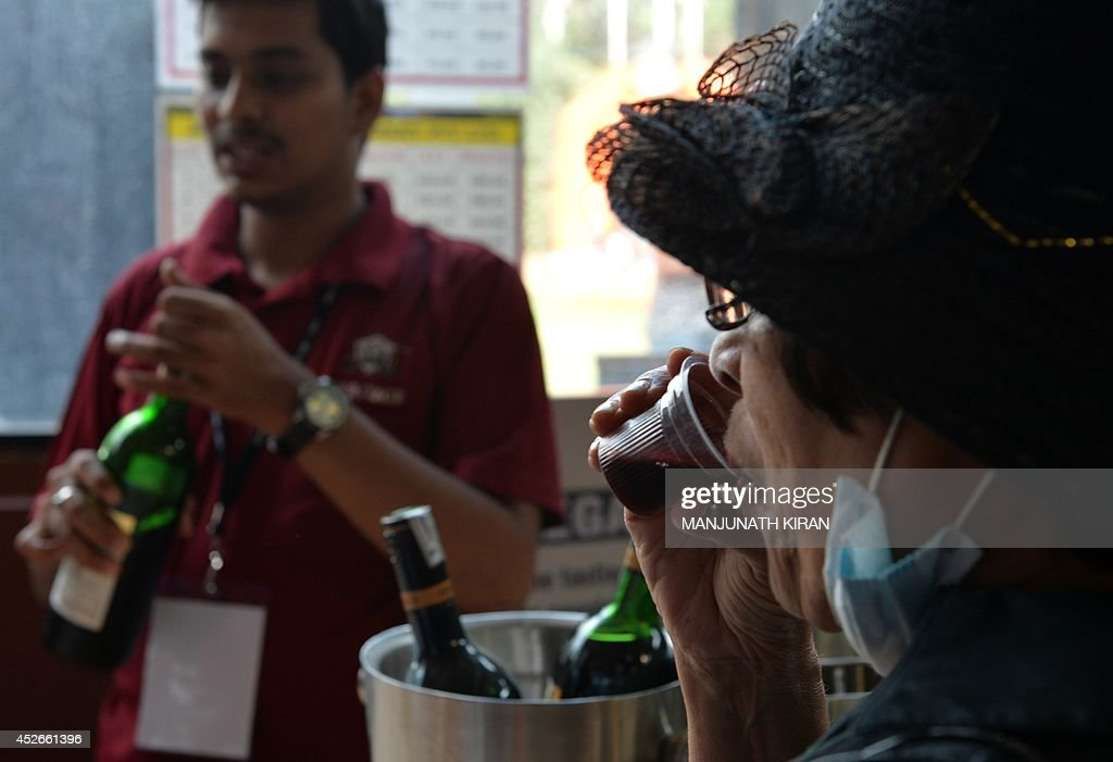 A visitor samples Indian wine during the International Wine Festival 2014 in Bangalore on July 25, 2014. The festival, which runs from July 25-27, aims to promote cultivation of grapes and encourage wine consumption. India's Karnataka state has seen a fourfold growth in cultivation of wine grape during the past six years, from 500 acres to 2,000 acres. The state during his period has also emerged as the second largest producer of wine grape and wine after Maharashtra state. Wine production touched 7.5 million litres in 2013-14, while Maharashtra stands at top position with 20 million litres per annum. AFP PHOTO/Manjunath KIRAN