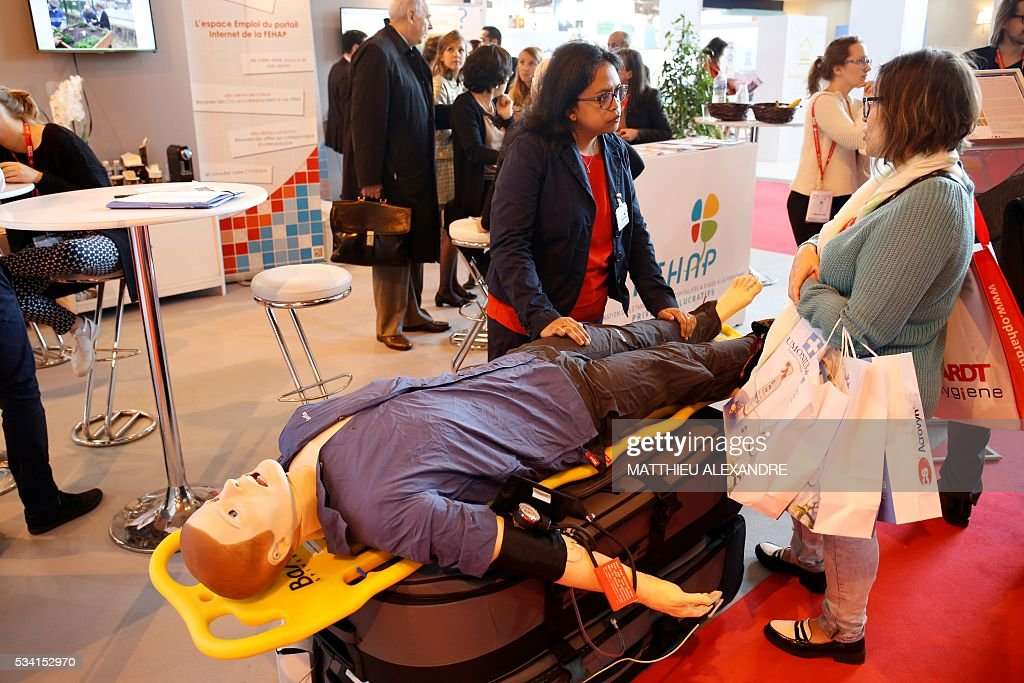 A visitor seeks advise at a stand during Paris Healthcare week on May 25, 2016 in the French capital. / AFP / MATTHIEU