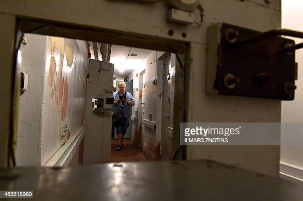 COLLIER A visitor seen through a flap walks past cells in the basement of the 'Stura maja' or 'Corner house' the former headquarters of the Soviet...