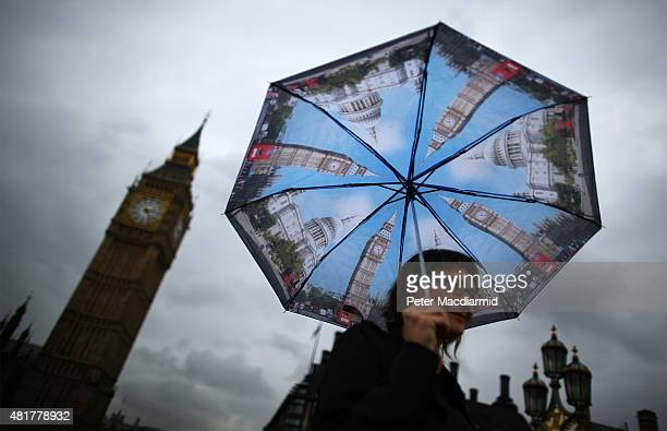 A visitor shelters from the rain under an umbrella decorated with images of Big Ben and St Paul's as she walks near Parliament on July 24 2015 in...