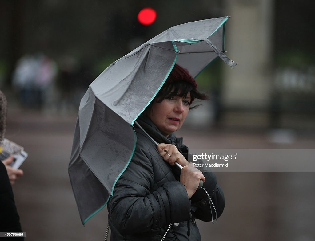 A visitor shelters under an umbrella in wet and windy conditions on December 30, 2013 in London, England. Parts of the United Kingdom are experiencing wintry conditions.