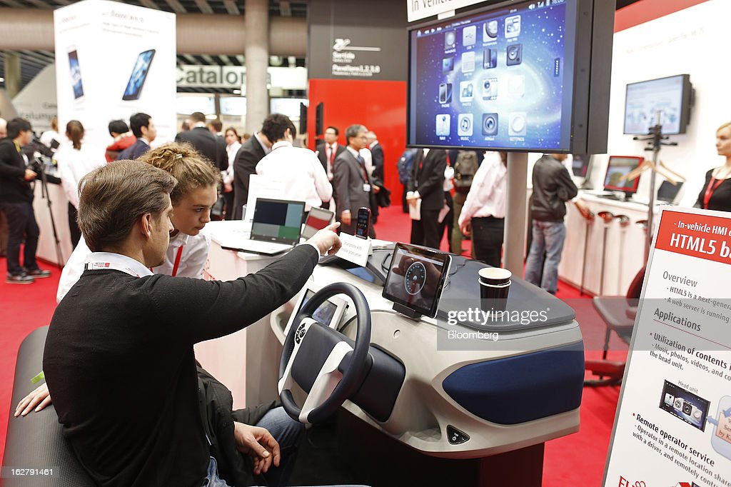 A visitor sits behind a steering wheel to test a vehicle infotainment system in the Fujitsu Ltd. pavilion at the Mobile World Congress in Barcelona, Spain, on Wednesday, Feb. 27, 2013. The Mobile World Congress, where 1,500 exhibitors converge to discuss the future of wireless communication, is a global showcase for the mobile technology industry and runs from Feb. 25 through Feb. 28. Photographer: Simon Dawson/Bloomberg via Getty Images