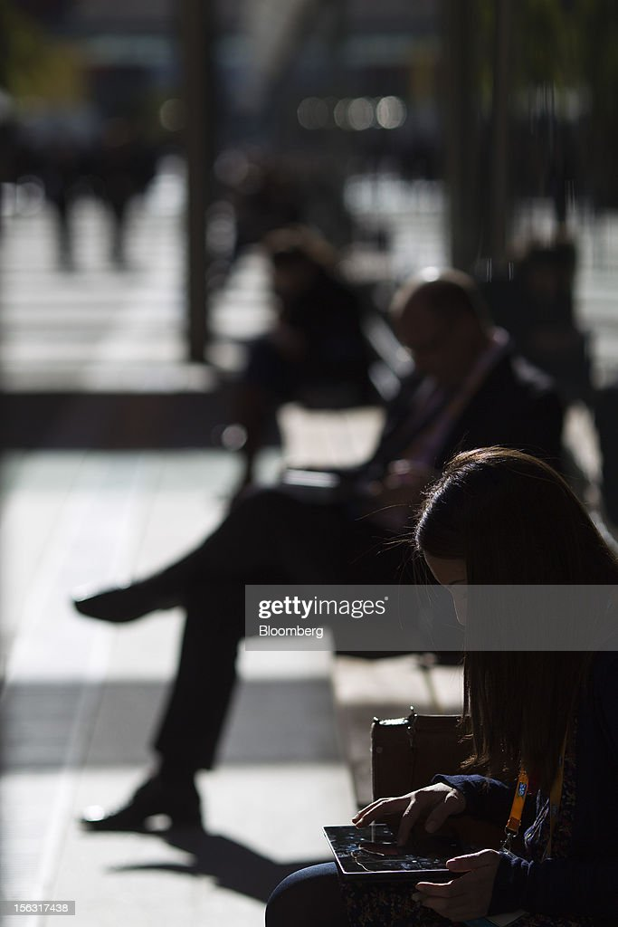 A visitor sits on a bench and checks her tablet computer during the opening day of the Sapphire Now conference in Madrid, Spain, on Tuesday, Nov. 13, 2012. SAP plans to deliver 6 SAP mobile apps for Windows 8. Photographer: Angel Navarrete/Bloomberg via Getty Images