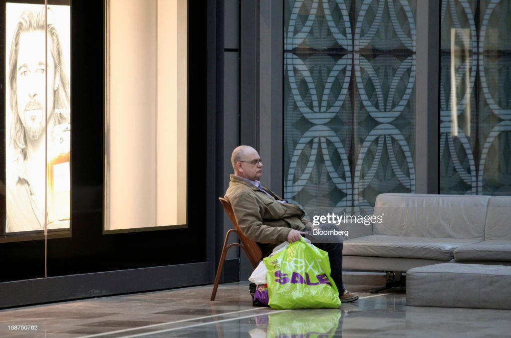 A visitor sits with shopping bags near a poster of U.S. actor Brad Pitt displayed in the window of a Chanel SA perfume store at the Westfield Stratford City shopping mall in London, U.K., on Thursday, Dec. 27, 2012. Overall Christmas shopping in the U.K. was similar to last year, according to the British Retail Consortium. Photographer: Chris Ratcliffe/Bloomberg via Getty Images