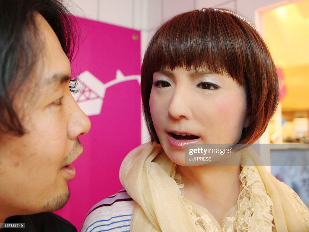 Visitor l smiles as he speaks with female humanoid robot minami