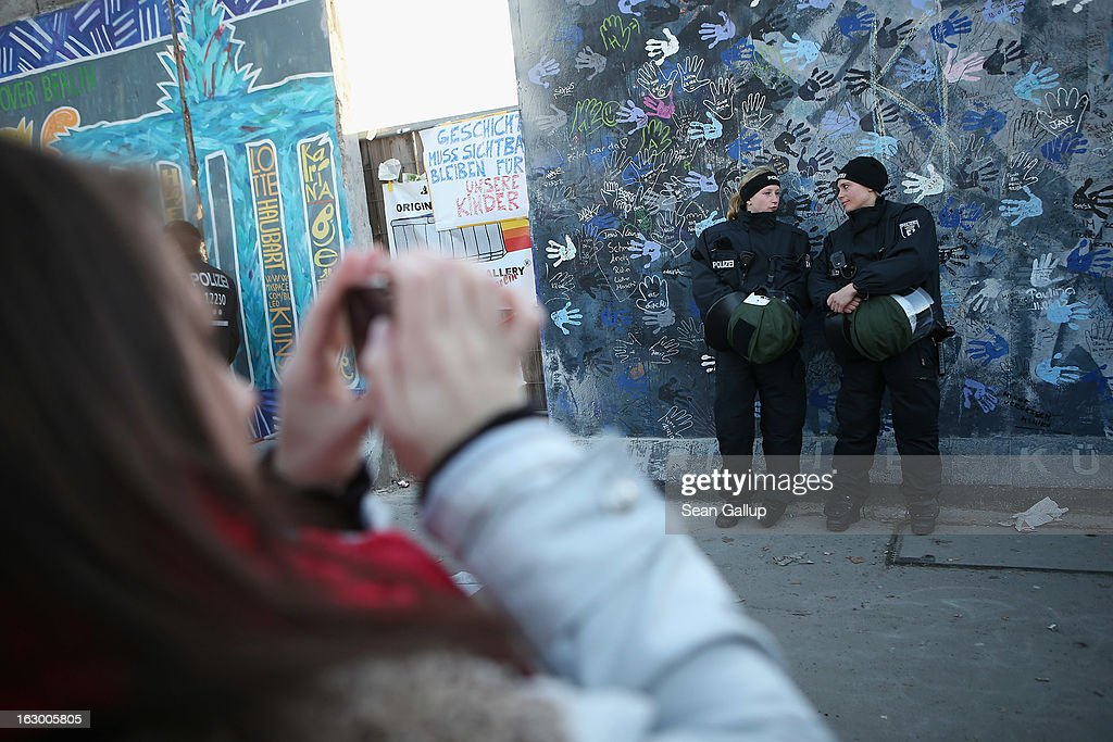A visitor snaps a picture as police in riot gear stand guard at a section of the East Side Gallery, which is the longest still-standing portion of the former Berlin Wall, that is to be removed tomorrow by a construction company building a high-rise luxury apartment block on March 3, 2013 in Berlin, Germany. A real estate developer is planning to build a 14-storey apartment building between the East Side Gallery and the Spree River and needs to remove the Wall section in order to allow access to the construction site. Protesters managed to temporarily halt the dismantling of the section on March 1. Critics, including East Side Gallery mural artists and Spree River embankment development opponents, decry the move, citing the importance of the East Side Gallery's status as a protected landmark and a major tourist attraction. The East Side Gallery is approximately 1.3 kilometers long.