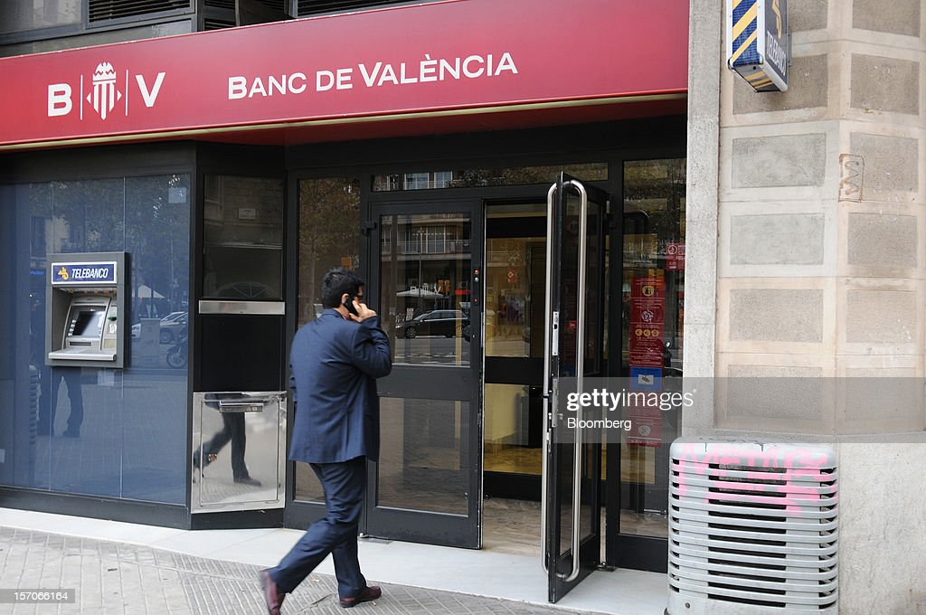 A visitor speaks on a mobile phone while entering a Banco de Valencia SA bank branch in Barcelona, Spain, on Wednesday, Nov. 28, 2012. Spanish banks getting European aid will shrink their balance sheets more than 60 percent, the European Commission said, as BFA-Bankia, the biggest rescued lender, expects to lose 19 billion euros ($25 billion) this year. Photographer: Stefano Buonamici/Bloomberg via Getty Images